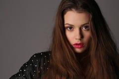 Flicka i ett dubbat läderomslag close upp Vit bakgrund Arkivfoton