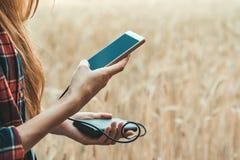 Flicka i ett gult fält som rymmer en telefon i hennes hand och laddar den från maktbanken royaltyfri foto