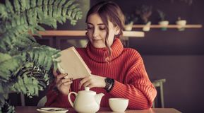 Flicka i ett kafé som dricker te Royaltyfria Bilder