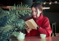 Flicka i ett kafé som dricker te Arkivbild