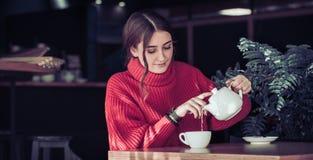 Flicka i ett kafé som dricker te Royaltyfri Fotografi