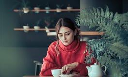 Flicka i ett kafé som dricker te Royaltyfri Foto