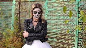 Flicka i ett läderomslag med makeup för allhelgonaafton på bakgrund av ett gammalt staket lager videofilmer