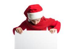 Flicka i ett lock av Santa Claus som ser en affisch Royaltyfri Bild