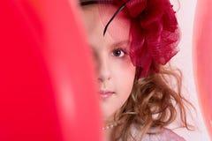 Flicka i ett rött hattnederlag bak en röd ballong Fotografering för Bildbyråer