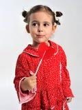 Flicka i ett rött klänninginnehav en klubba Royaltyfri Fotografi