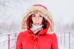 Flicka i ett rött lag med en huv som går i parkera Royaltyfria Foton