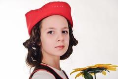 Flicka i ett rött lock med en solros Fotografering för Bildbyråer