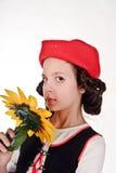 Flicka i ett rött lock med en solros Arkivbild