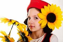 Flicka i ett rött lock med en solros Arkivbilder