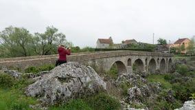 flicka i ett rött omslag som tar bild den roman bron Gammal bro för sten i en liten by av Montenegro arkivfoton