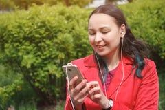 Flicka i ett r?tt omslag i Park som lyssnar till musik med h?rlurarearbuds med en smartphone i hand arkivbild