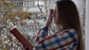 Flicka i ett rutigt skjortaanseende på balkongen vid fönstret och läsningen en bok på bakgrunden av blommande aprikors stock video