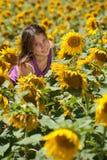 Flicka i ett solrosfält Fotografering för Bildbyråer