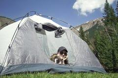 Flicka i ett tält utomhus arkivbild