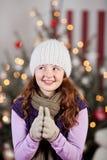Flicka i ett ulligt lock med en julgran Royaltyfri Foto