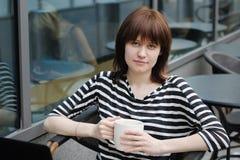 Flicka i ett utomhus- kafé Arkivfoto