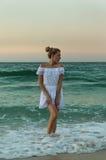 Flicka i ett vitt klänninganseende i vattnet royaltyfria bilder