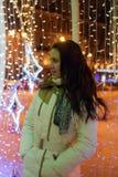 Flicka i ett vitt lag i vinter och glödande julgirland royaltyfri fotografi