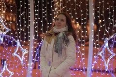 Flicka i ett vitt lag i vinter och glödande julgirland arkivbilder