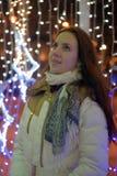 Flicka i ett vitt lag i vinter och glödande julgirland royaltyfri foto