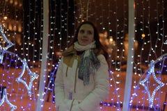 Flicka i ett vitt lag i vinter och glödande julgirland arkivbild