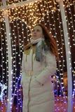 Flicka i ett vitt lag i vinter och glödande julgirland royaltyfria bilder