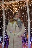 Flicka i ett vitt lag i vinter och glödande julgirland fotografering för bildbyråer