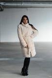 Flicka i ett vitt pälslag som poserar i studio Royaltyfri Foto