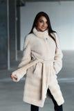 Flicka i ett vitt pälslag som poserar i studio Royaltyfri Fotografi