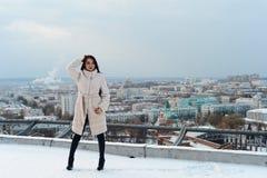 Flicka i ett vitt pälslag som poserar mot bakgrunden av staden Royaltyfri Bild