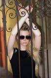Flicka i exponeringsglas och en svart klänning på gatan Royaltyfri Foto