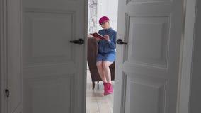 Flicka i exponeringsglas på stolen som läser en bok i vitt rum arkivfilmer