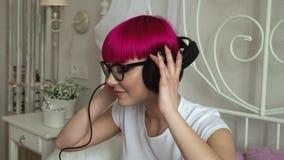 Flicka i exponeringsglas som lyssnar till musik på hörlurar stock video