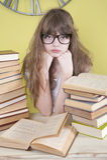 Flicka i exponeringsglas som sitter bak böcker Royaltyfria Foton