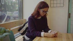 Flicka i exponeringsglas som sitter i kafét och bläddrar internet på smartphonen stock video