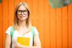 Flicka i exponeringsglas som står på det orange staketet Arkivbild