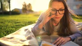 Flicka i exponeringsglasläseboken som ner ligger på en filt i parkera på solnedgången lager videofilmer