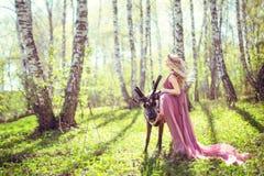 Flicka i felik klänning och ren i skogen Royaltyfri Bild