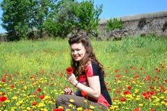 Flicka i filden av lösa blommor (vallmo och calend Royaltyfri Bild