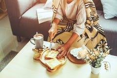 Flicka i filt som kopplar av på soffan i vardagsrum Royaltyfria Bilder