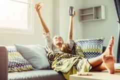 Flicka i filt som kopplar av på soffan i vardagsrum Royaltyfri Bild