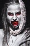 Flicka i formen av levande död, allhelgonaaftonlik med blod på hans kanter Bild för en rysare Royaltyfria Bilder