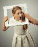 Flicka i fotoram Arkivbilder