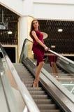Flicka i gallerian på rulltrappan Arkivbild
