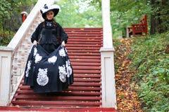 Flicka i gammal retro klänning på utomhus- trappa Royaltyfri Bild