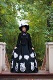 Flicka i gammal retro klänning på utomhus- trappa Arkivfoton