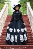 Flicka i gammal retro klänning på utomhus- trappa Arkivbild