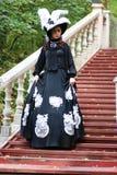 Flicka i gammal retro klänning på utomhus- trappa Royaltyfri Foto