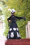 Flicka i gammal retro klänning på utomhus- trappa Arkivbilder